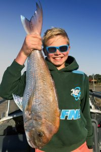 Red alert: Harvey Kilpatrick with the 63 cm snapper that he caught offshore from Portarlington last week (Picture: Greg Kilpatrick).