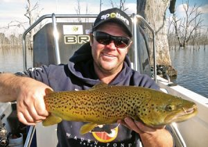 Clint Hotchin with a brown trout he caught from Lake Toolondo recently (Picture: Victorian Inland Charters).