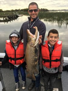 Team effort: Chris Farrugia, with his sons Charlie and Cooper and the 4.6 kg brown trout he caught from Lake Purrumbete on Friday morning (Picture: Lake Purrumbete Holiday Park).